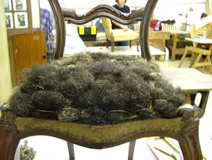 Picture of stripped chair being stuffed with horsehair